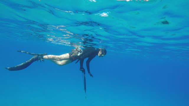 Male spear fisherman dives below surface