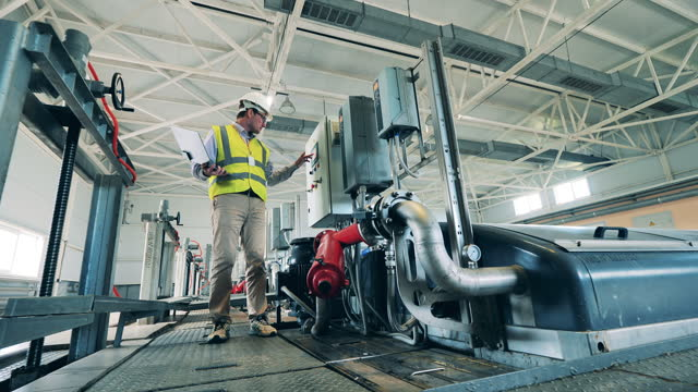 Male specialist inspecting an indoor sewage treatment system using a laptop video