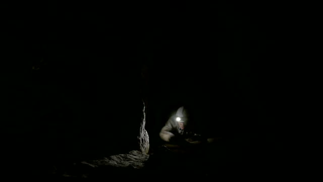 male speleologist was grabbed by the foot in the dark narrow cave - horror - кейвинг стоковые видео и кадры b-roll