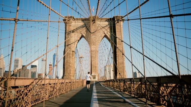 日当たりの良い夏の日にニューヨークのブルックリン橋に沿って実行している男性のスポーツマン。美しい建築物低角度のショットを 4 k - 対称点の映像素材/bロール