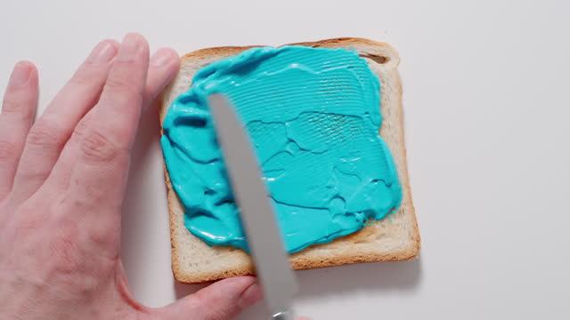 vídeos y material grabado en eventos de stock de macho esparciendo pasta azul en una tostada con cuchillo. vista superior. - ingrediente