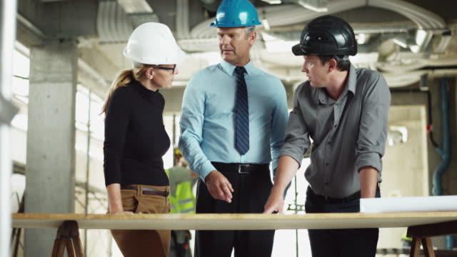 DS Male structural engineer and female architect going over the plans with project manager at the construction site video