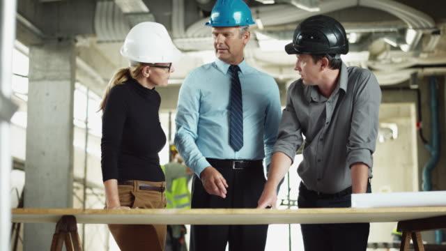 Ingénieur en structure DS mâle et femelle architecte reprenant les plans avec le chef de projet sur le chantier - Vidéo