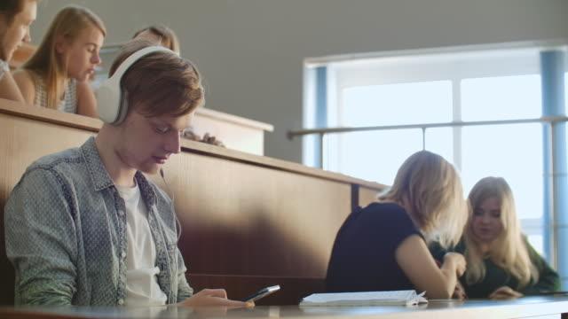 ein männlicher student in einem auditorium der universität hört während einer pause musik in weißen kopfhörern, ohne auf andere zu achten. viele leute im publikum reden - vorlesungsfrei stock-videos und b-roll-filmmaterial