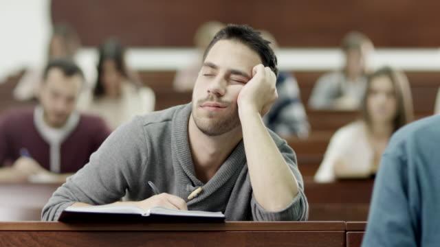 Estudiante masculino dormir en montaje tipo aula - vídeo