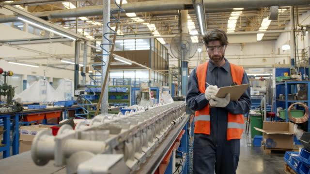 vídeos y material grabado en eventos de stock de supervisor masculino revisando una estación de trabajo con tubos en una fábrica de bombas de agua de fabricación - material de construcción
