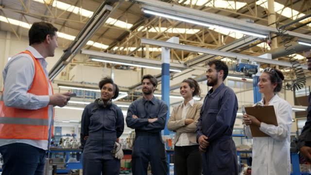 manlig handledare gratulera blue collar arbetstagare under ett personalmöte medan de handslag och alla applåderar - kroppsarbetare bildbanksvideor och videomaterial från bakom kulisserna