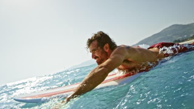 slo mo männliche surfer paddeln auf dem board im ozean - nackter oberkörper stock-videos und b-roll-filmmaterial