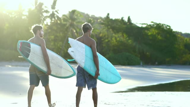 Male surfers walk on beach. Fitness friends with surfboards looking at the ocean