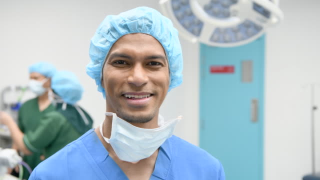 Male surgeon in scrubs smiling at camera