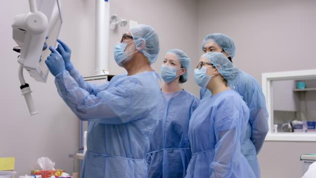 vídeos y material grabado en eventos de stock de el cirujano masculino revisa la condición médica del paciente con el equipo quirúrgico antes de la operación - cirugía