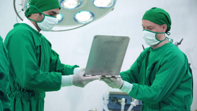 Male surgeon signing document in hospital operating room