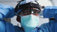 istock Male Surgeon With Protective Glasses And Head Light Putting On Mask In Hospital Operating Theater 1206874684