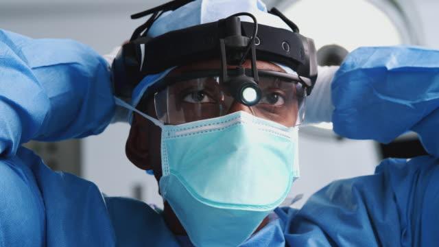 男性外科醫生與保護眼鏡和頭燈在醫院手術室戴上口罩 - surgeon 個影片檔及 b 捲影像