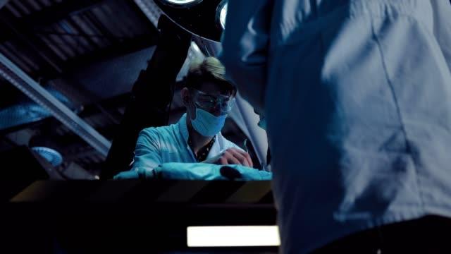 vídeos y material grabado en eventos de stock de los cirujanos masculinos realizan una operación en el laboratorio de la nave espacial. los asistentes de laboratorio están vestidos con batas blancas y vasos, la iluminación está funcionando. - autopsia