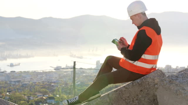 Male surveyor sitting on concrete at his outdoor workplace against of sun video