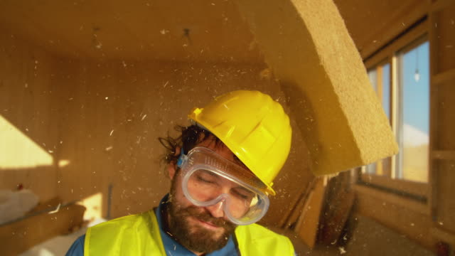 close up: male surveyor with a beard gets struck in the head by a piece of foam. - poliuretano polimero video stock e b–roll