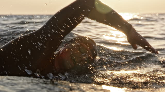 SLO MO TS Male swimmer swimming front crawl at sea in sunshine Slow motion medium tracking shot of a male open water swimmer swimming front crawl at sea in sunshine. Shot in Slovenia. swimming stock videos & royalty-free footage