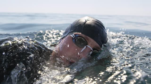 vídeos de stock e filmes b-roll de slo mo ts male swimmer swimming front crawl in sunshine - swim arms