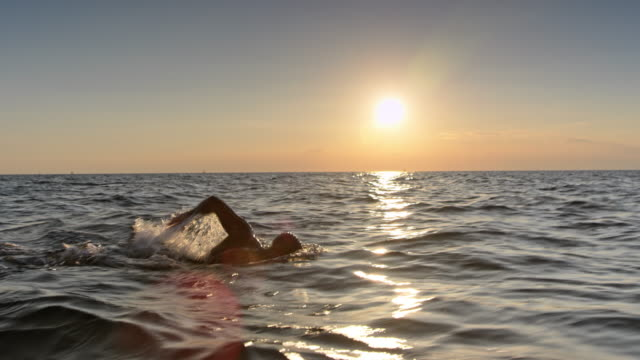 TS Male swimmer swimming front crawl in the choppy sea at sunset Wide tracking shot of a male open water swimmer swimming forward crawl in the choppy sea at sunset. Shot in Slovenia. wristwatch stock videos & royalty-free footage