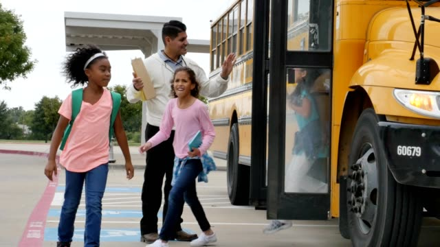 male teacher greets diverse school children as they disembark from a school bus - teacher stock videos & royalty-free footage