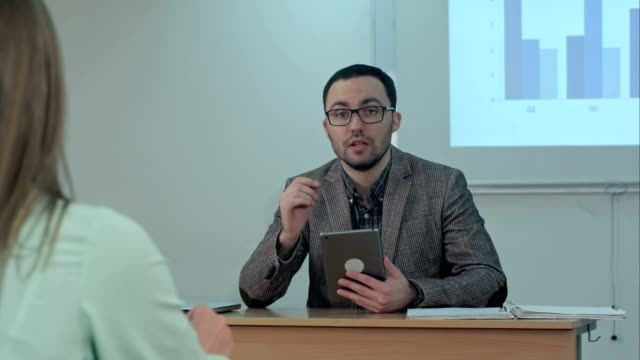 Male teacher holding digital tablet sitting in front of students and talk to a camera video