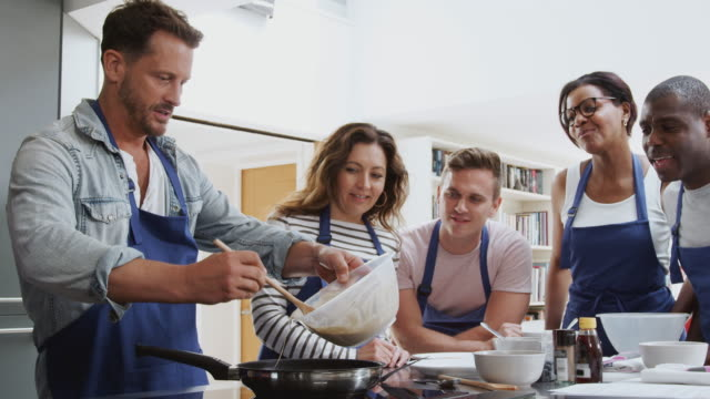 male teacher making flatbread on cooker in cookery class as adult students look on - cibi e bevande video stock e b–roll