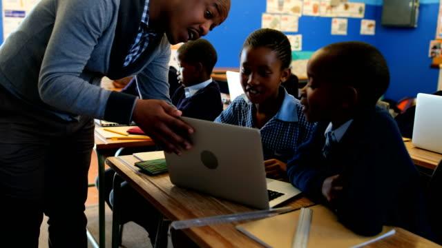 stockvideo's en b-roll-footage met mannelijke leraar lesgeven van studenten op de laptop in de klas 4k - kindertijd