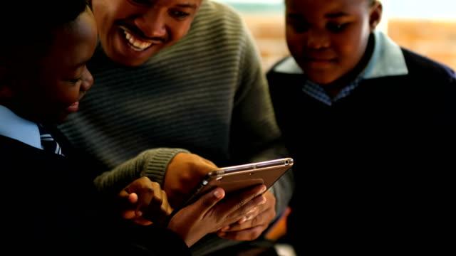 manlig lärare använder digitala tablett med elever i klassrum 4k - digital reading child bildbanksvideor och videomaterial från bakom kulisserna