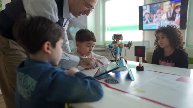 männlicher lehrer mit kindern, die spaß am unterricht in der privatschule haben - grundschule stock-videos und b-roll-filmmaterial
