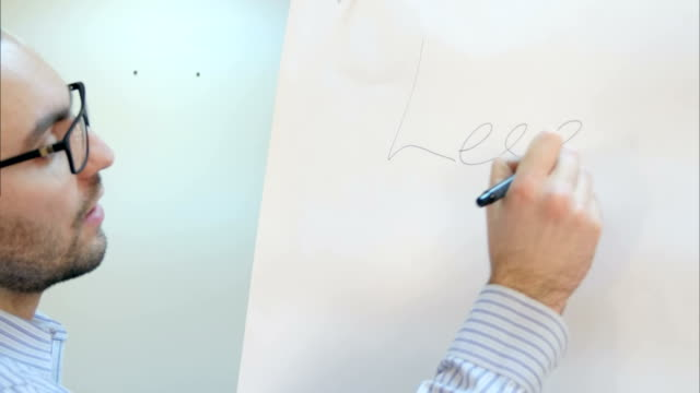 Male teacher writes on the board at the seminar video