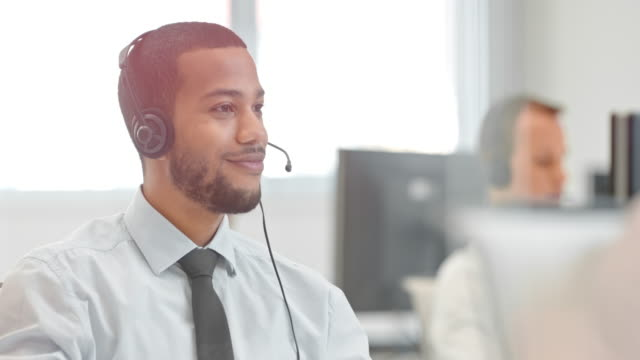 DS Male technical support telephone operator talking to a client Medium dolly shot of a telephone operator in a technical support call center talking over the phone with a client guiding him through the procedure. call centre videos stock videos & royalty-free footage