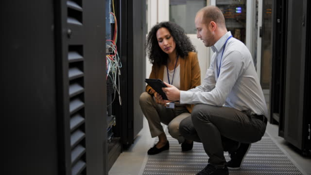 DS Male technician talking to his female colleague in the server room Medium dolly shot of a technician and his female colleague discussing the connections on the server rack  while squatting in the server room. server room stock videos & royalty-free footage