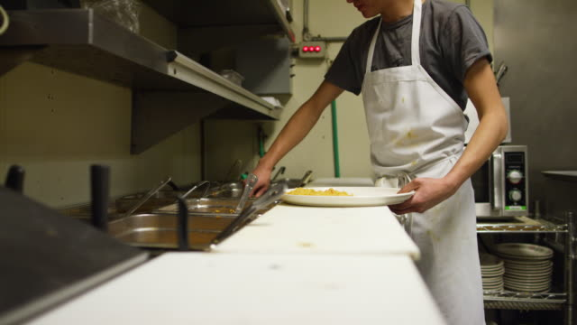 A Male, Teenage Cook Spoons Beans on to a Plate from a Food Bar in a Commercial Kitchen at a Mexican Restaurant