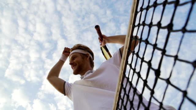stockvideo's en b-roll-footage met tennisser genieten van zijn overwinning op tennis kampioenschap, verhogen handen - kampioenschap