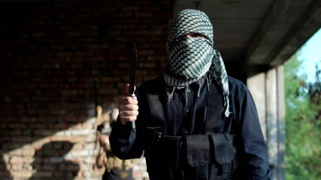 Male terrorist making demands at camera
