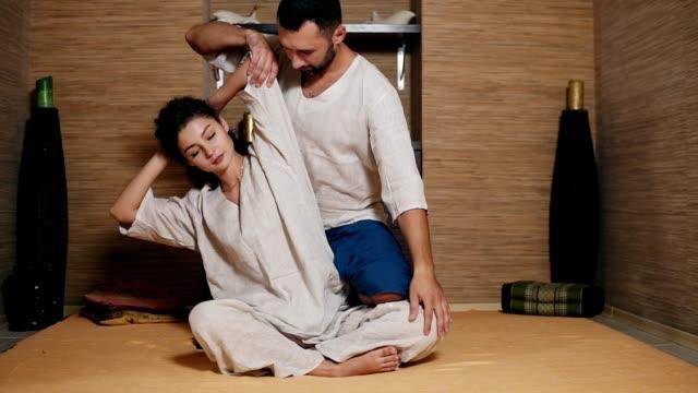 男性タイ按摩若い女性の側の彼女の後ろに座っていると、彼女の手と膝を押し、ストレッチです。目を閉じながら美しい少女がタイ式マッサージを受信します。 - 髪型点の映像素材/bロール