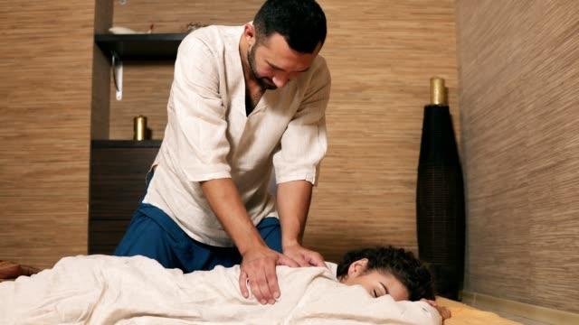 male thai massagist is treating young woman's back and shoulder. thai massage session for young attractive woman in kimono. shot in 4k - kosmetyczka praca w salonie piękności filmów i materiałów b-roll