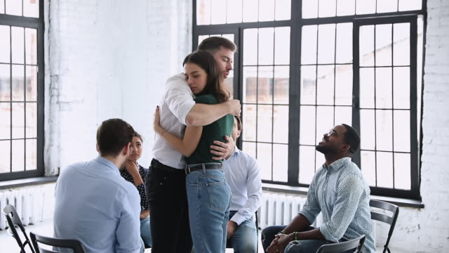 male therapist embracing female patient giving support during group therapy - assuefazione video stock e b–roll