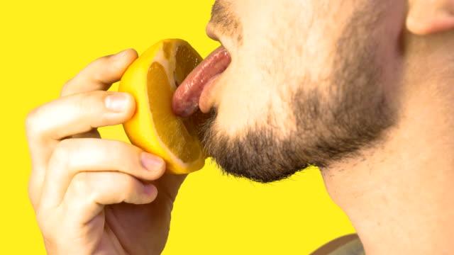 erkek dil yalama dilimli turuncu taklit cunnilingus sarı arka plan üzerinde. seks konsepti. cinsel meyve yeme. taklit oral seks - üreme organı stok videoları ve detay görüntü çekimi