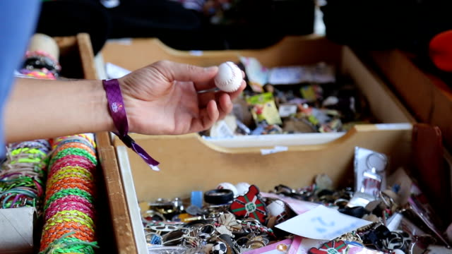 male tourist choosing key ring souvenir from wooden box at local street market - key ring stock videos & royalty-free footage