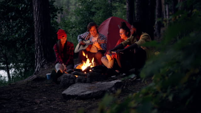 Male tourist is playing the guitar while his relaxed friends are listening and throwing firewood in campfire sitting together near tent in forest. Music and friendship concept.