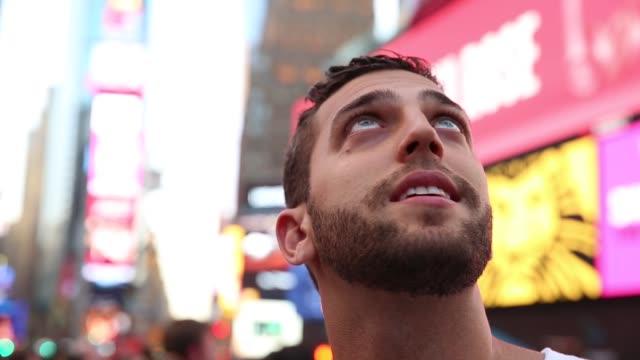 turista maschio che osserva le luci di times square - guardare in su video stock e b–roll