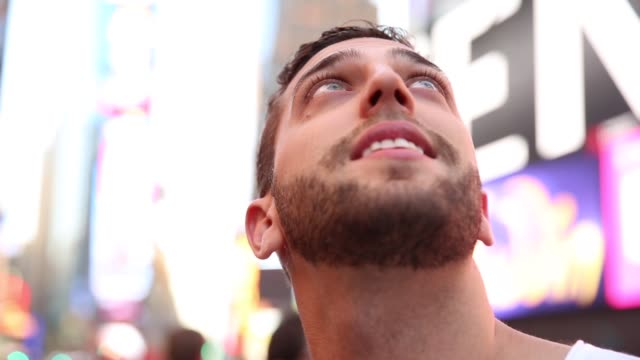 male tourist observing the lights of the times square - curiosità video stock e b–roll