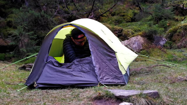A male tourist opens a tent set in nature in the mountains and crawls out of it. Tourism in the mountains of the Carpathians, Ukraine. Prores 422