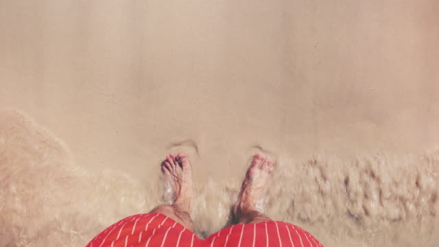 Male Tourist Standing on a Beach Point of view shot of a man standing on a beach with his feet in the water. Shot in 4K resolution. foot stock videos & royalty-free footage