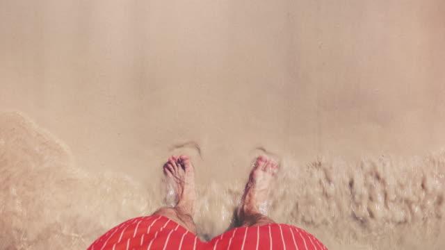 vídeos de stock e filmes b-roll de male tourist standing on a beach - sand