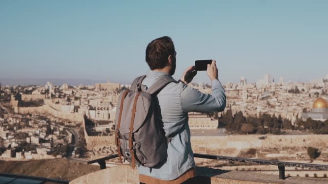 Male tourist takes smartphone photos of Jerusalem. European bearded man enjoys ancient town scenery. Israel. Slow motion video