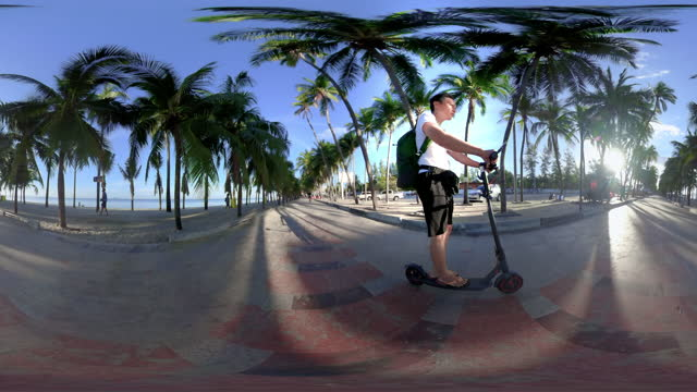 360 Male tourists riding e-scooter on the beach