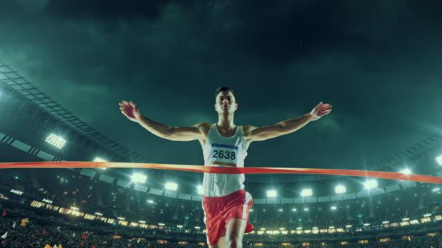 vídeos y material grabado en eventos de stock de atletismo masculino corredor cruza la línea de llegada - meta